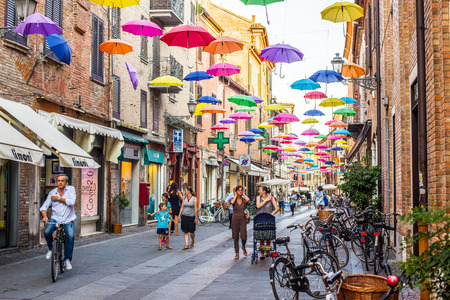 via: Cyclists crossing Via Giuseppe Mazzini of Ferrara covered with umbrellas colored. Emilia-Romagna. Italy.