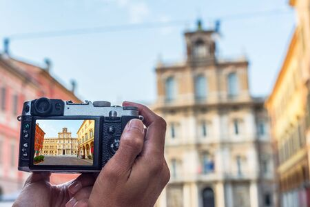 ducale: Male hands taking a photo of Palazzo Ducale in Piazza Roma of Modena. Emilia-Romagna. Italy.