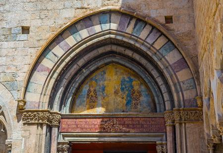 portico: Mural in the tympanum of portico in the south facade of Basilica of Sant Feliu in Gerona. Costa Brava, Catalonia, Spain. Stock Photo