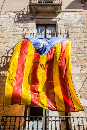 separatist: Flag of independence movement of Catalonia, called Estelada (unofficial), waving in a street of the downtown of Girona, Costa Brava, Catalonia, Spain.