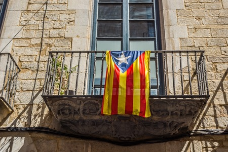 unofficial: Flag of independence movement of Catalonia, called Estelada (unofficial), in a street of the downtown of Girona, Costa Brava, Catalonia, Spain.