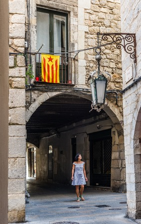unofficial: Latin American women walking under a flag of independence movement of Catalonia, called Estelada (unofficial), in a street of the downtown of Girona, Costa Brava, Catalonia, Spain.