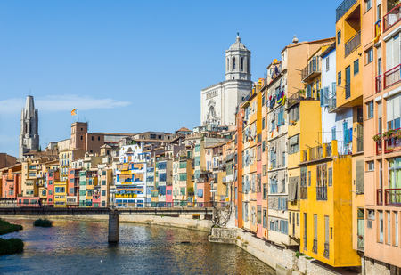 Onyar river crossing the downtown of Girona with bell tower of Basilica of Sant Feliu and Santa Maria cathedral in background. Gerona, Costa Brava, Catalonia, Spain. Stock Photo