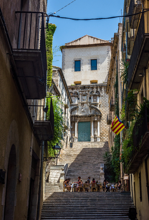 unofficial: Pujada Sant Domenec street with a flag of independence movement of Catalonia, called Estelada (unofficial), in a balcony and Sant Marti Sacosta church in background. Girona, Costa Brava, Catalonia, Spain.
