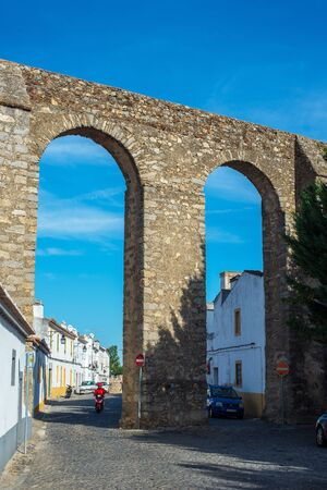 aquifer: Street in the downtown of Evora, with a motorcycle crossing to arch of archaeological remains of a Roman aqueduct. Evora, Alentejo. Portugal. Editorial