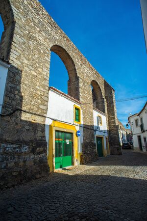 patrimony: Evora, Portugal - November 29, 2016. Archs of archaeological remains of a Roman aqueduct in the downtown of Evora, Alentejo. Portugal.