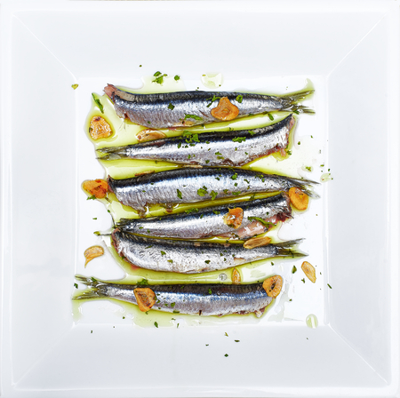 Anchovies marinated in olive oil and cooked at a low temperature on a white plate.