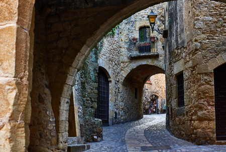 Doorgang of Carrer Major street in the medieval historic downtown of Pals. Bajo Ampurdan, Girona, Catalonia, Spain.