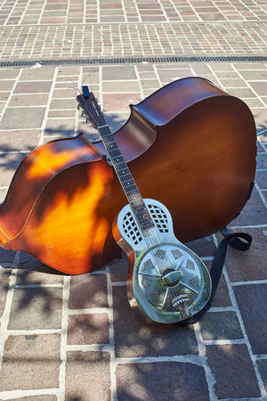 resonator: Metallic resonator acoustic guitar leaning on a cello. Also known as National. Editorial