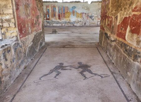 Mosaics at entrance of archaeological remains of Palestra Palestri Dei Luvenes  in Ruins of Pompeii. The city was an ancient Roman city destroyed by the volcano Vesuvius. Pompei, Campania, Italy.
