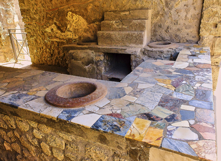 Thermopolium of archaeological remains of Via della Abbondanza street at Ruins of Pompeii. The city was an ancient Roman city destroyed by the volcano Vesuvius. Pompei, Campania, Italy.
