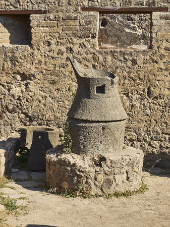 A roman stone hand mill (mola asinaria) of a bakery at Ruins of Pompeii. The city was an ancient Roman city destroyed by the volcano Vesuvius. Pompei, Campania, Italy.