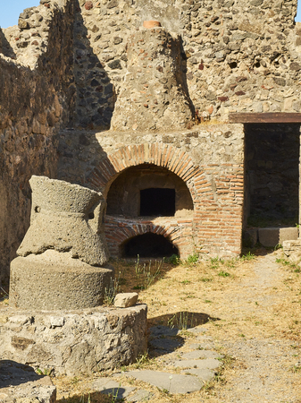 Roman oven and stone hand mill (mola asinaria) of a bakery of archaeological remains at Ruins of Pompeii. The city was an ancient Roman city destroyed by the volcano Vesuvius. Pompei, Campania, Italy.
