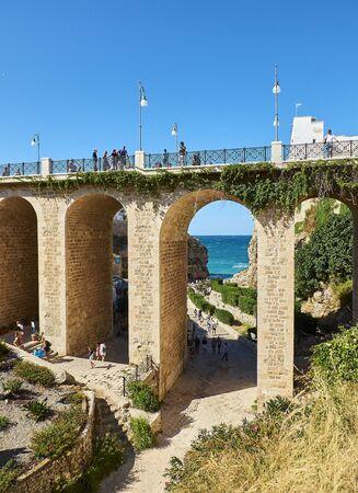 Polignano a Mare, Italy - August 13, 2017. Ponte di Polignano bridge with Lama Monachile Cala Porto beach in background. Apulia, Italy.