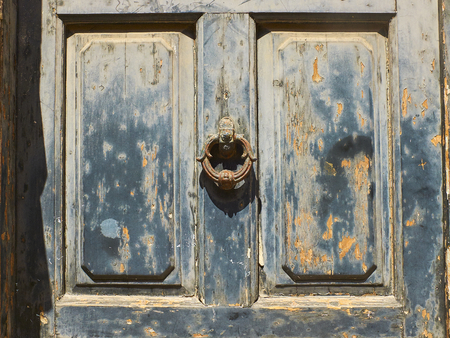 Weathered wooden door with a rusty metal ring knob textured with blue paint chipped and peeling.