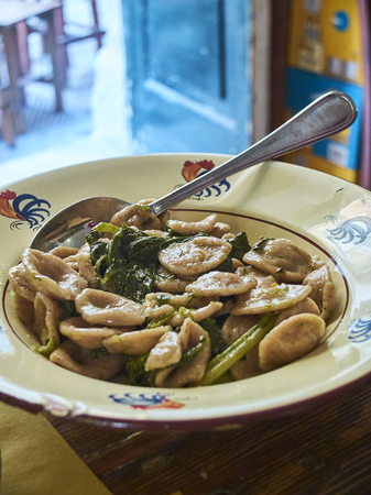 Typical orecchiette pasta of Puglia on a rustic presentation of a trattoria in Lecce, with Cime di rapa, Broccoli raab or Broccoli rabe, a green cruciferous vegetable.