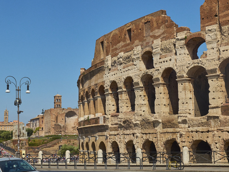 The roman Colosseum (also known as Flavian Amphitheatre) with the Temple of Venus and Rome and Santa Francesca Romana bell tower in background.