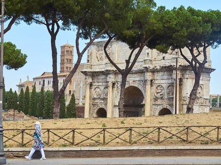 Rome, Italy - August 19, 2017. Arco de Constantino, Arch of Constantine, with Santa Francesca Romana bell tower in background and a tourist going through Via Celio Vibenna in foreground. Rome, Lazio, Italy. Editorial