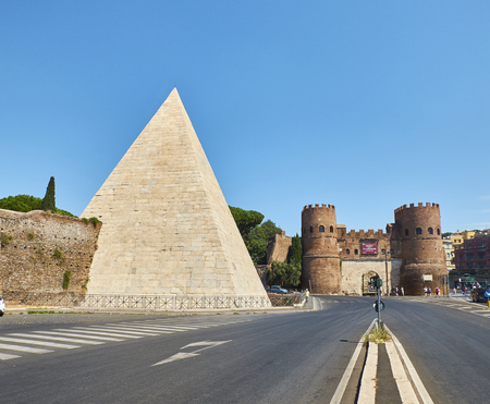 Rome, Italië - 19 augustus 2017. De Piramide van Cestius (Piramide di Caio Cestio of Piramide Cestia) en Porta San Paolo hek in de achtergrond. Uitzicht vanaf het plein Piazzale Ostiense. Rome, Lazio, Italië.