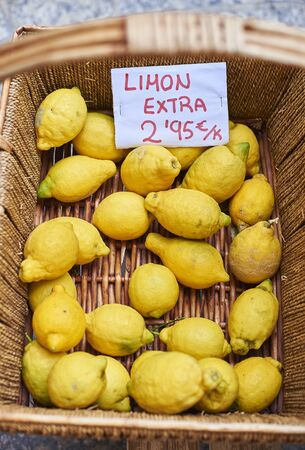 Ecological lemons in a wicker basket of a market. (Cartel in spanish showing the price)