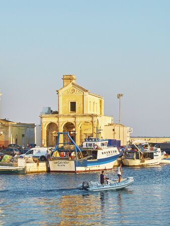 Gallipoli, Italy - August 17, 2017. Fishing boatst in the fishing port of Gallipoli at sunset with La Madonna del Canneto church in background. Puglia, Italy.