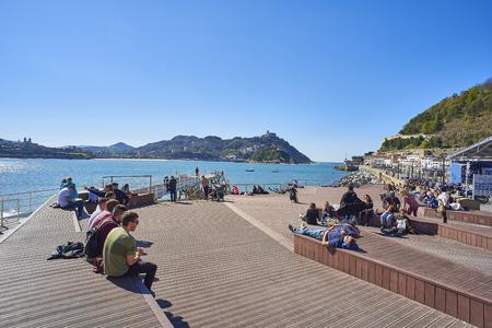 San Sebastian (Donostia), Spain - March 16. People enjoying a sunbathing in footbridge of leisure harbour of San Sebastian with Santa Clara island and Monte Igueldo in background. Basque Country, Guipuzcoa. Spain.