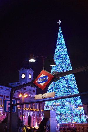 Madrid, Spain - December 12, 2017. Puerta del Sol metro station signboard at night with Real Casa de Correos illuminated by christmas lights and a shinny christmas tree in background. Editorial