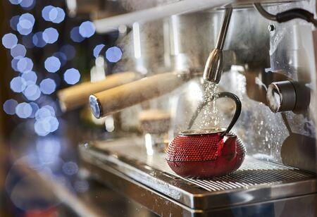 Making a tea in a red tetsubin with a classic Italian coffee machine. Stock Photo