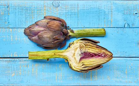 A purple artichoke sliced over a mediterranean blue wooden table.