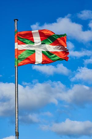 Ikurrina, Basque Country flag waving on a blue sky. Spain.