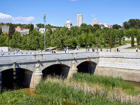Madrid, Spain - May 15, 2018. Puente del Rey bridge over the Manzanares river in Madrid Rio at spring day with Principe Pio and Plaza de Espana in background.