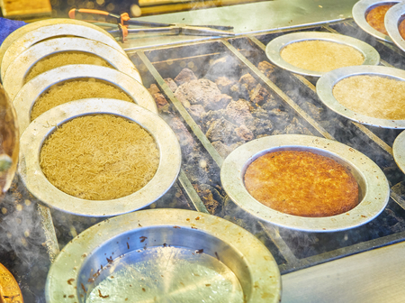 Cooking Kunefe, also known as Kenafeh, a traditional Arab dessert made with Kadayif, a thin pastry noodle, over a charcoal grill.