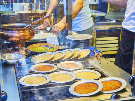 Cooking Kunefe, also known as Kenafeh, a traditional Arab dessert made with Kadayif, a thin pastry noodle, over a charcoal grill of a street stall in Istanbul.
