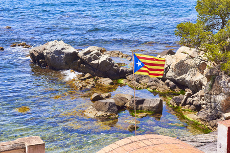 Flag of independence movement of Catalonia, called Estelada (unofficial), in Cala SAlguer Cove of Palamos, Girona, Costa Brava, Catalonia, Spain.