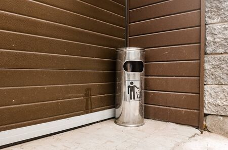 Street metal trash with an ashtray standing in the corner near the building with a bottom angle