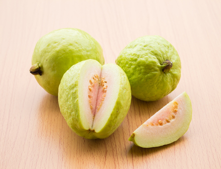 Fresh guava fruit is placed on a wooden floor.