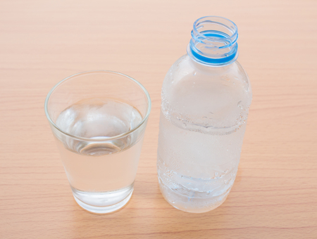 Water bottle and a glass of water placed on a wooden floor. Stock Photo