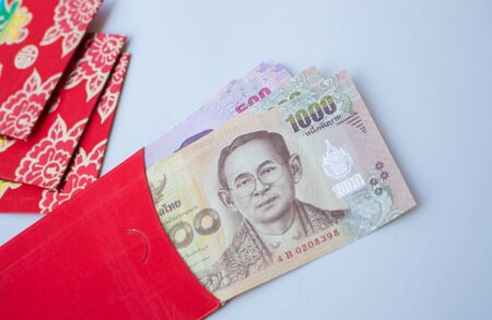 Chinese New Year red envelope with banknotes placed on a white background given to children and elders during chinese new year for blessing