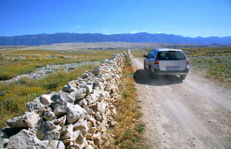 Sandy road from the main road leading to the beach called Zrće on the island of Pag and car is heading in direction of a beach. Stock Photo