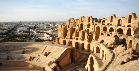 tunis: Amphitheatre with El Djem city skyline in Tunisia  Arches and auditorium of roman biggest amphitheater in africa with city skyline of El Djam in the background, Tunisia