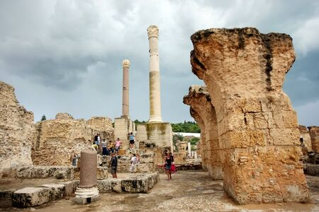 passageways: Antonine Baths columns   General view of Antonine Baths  Center of ruins under rainy and stormy weather with tourists who are visiting ruins  Stock Photo