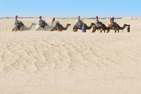 Douz, Kebili, Tunisia - September 17, 2012   Beduins leading tourists on camels at the Sahara desert on September 17, 2012 in Douz, Kebili, Tunisia