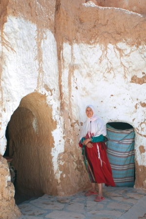 MATMATA, TUNISIA - SEPTEMBER 17  The largest region of the troglodyte communities  One of many dwellings - fragment of courtyard excavated in the rock  circular crater a few meters deep  on September 17, 2012 in Matmata, Tunisia  Unidentified berber woman Stock Photo - 19851274