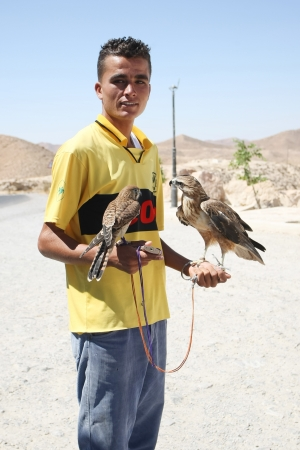 beggars: Matmata, Tunisia -  September 17th, 2012    One of the beggars with two hawks holding in his hands on the tourist point in Matmata, Tunisia  Beggars are typical occurrence in Tunisia  Wherever there are tourists and tourist point, beggars come with a vari Editorial