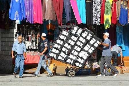 shoe boxes: T�nez, T�nez - 14 de septiembre 2012 Dos hombres que empujan un tranv�a lleno de cajas de zapatos apiladas en la Medina, famoso mercado de T�nez, T�nez Editorial