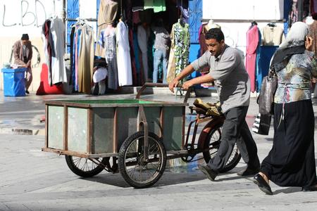 Tunisi, Tunisia - 14 Settembre 2012 Man spingendo un triciclo, bici rinnovato che � destinato per il mercato nella medina, famoso mercato di Tunisi, Tunisia