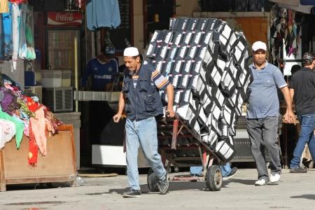 shoe boxes: T�nez, T�nez - 14 de septiembre 2012 Dos hombres que empujan un carrito lleno de cajas de zapatos apiladas en la medina, el famoso mercado de T�nez, T�nez Editorial