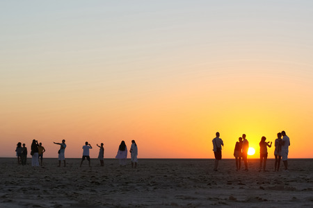 Chott El Jerid,Tunisia - September 17th, 2012   Tourists watching and photographing the sunrise at Chott El Jerid, a large salt lake in southern Tunisia  Chott El Jerid is the largest salt pan of the Sahara and it can be crossed by foot