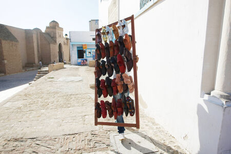 Kaioruan, Tunisia - September 16th   A muslim man selling shoes in front of the Great Mosque in the street of Kairouan, Tunisia