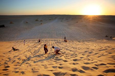 Ong Jemel, Tunisia - 17 Settembre 2012 turisti che si godono il tramonto rotolare gi� per la duna di sabbia a una fermata turistico vicino Ong Jemel, Tozeur, Tunisia Editoriali